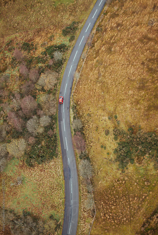 A red car driving along a country road by Andy Campbell for Stocksy United