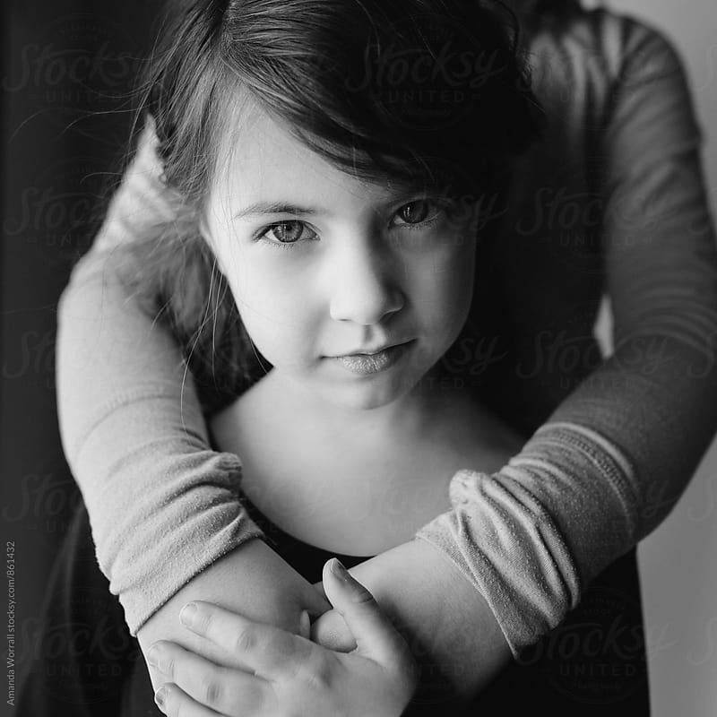 Black and white portrait of a young girl looking at the camera by Amanda Worrall for Stocksy United