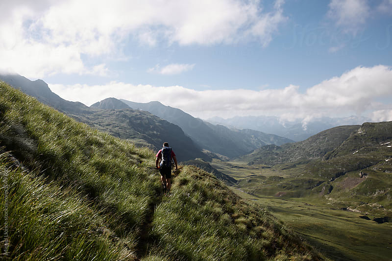 Scenic view of hiker in a long distance moutain trail by Miquel Llonch for Stocksy United