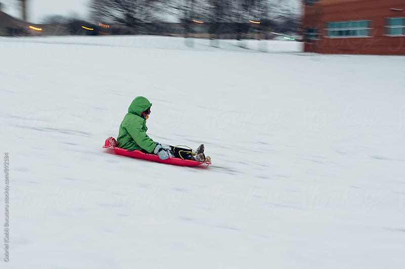 Black girl sledding on a hill by Gabriel (Gabi) Bucataru for Stocksy United