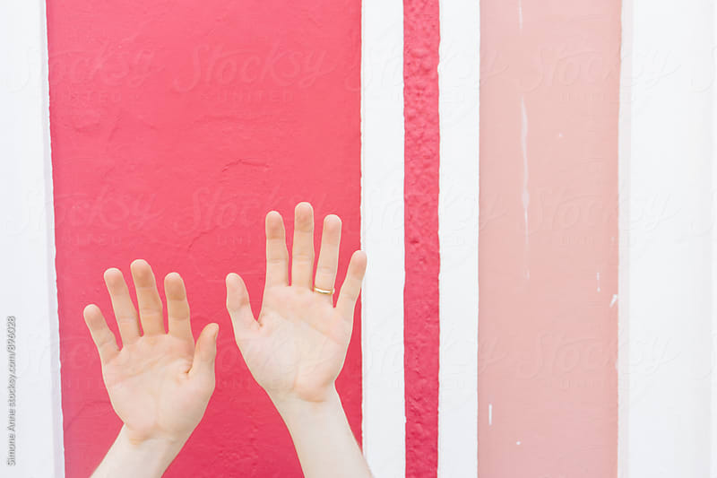 Man's hands against a pink wall by Simone Anne for Stocksy United