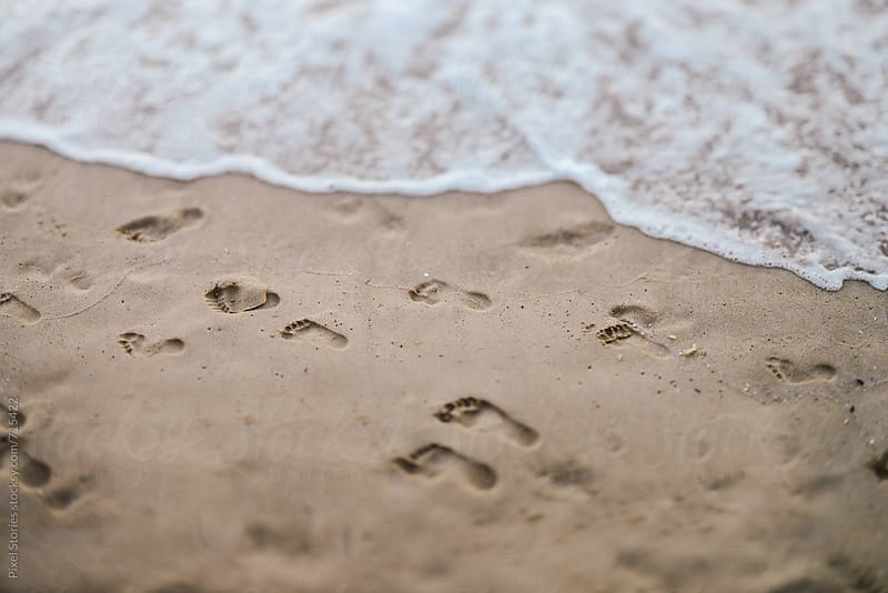 Footsteps on sandy beach by Pixel Stories for Stocksy United