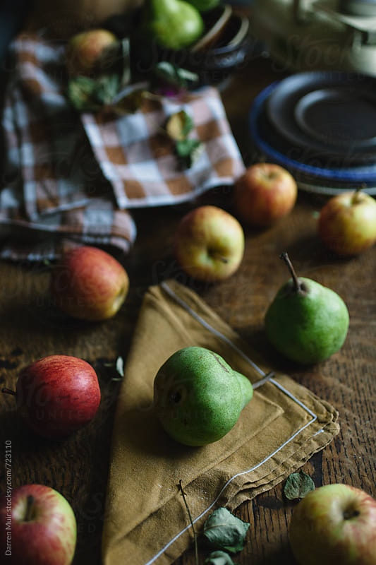 Apples and pears scattered over a table. by Darren Muir for Stocksy United