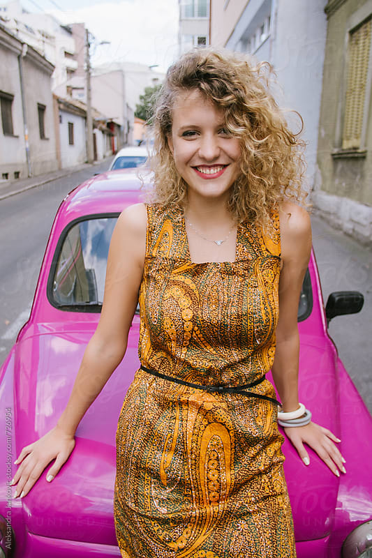 Attractive Blond Woman Leaning Against the Small Pink Car  by Aleksandra Jankovic for Stocksy United