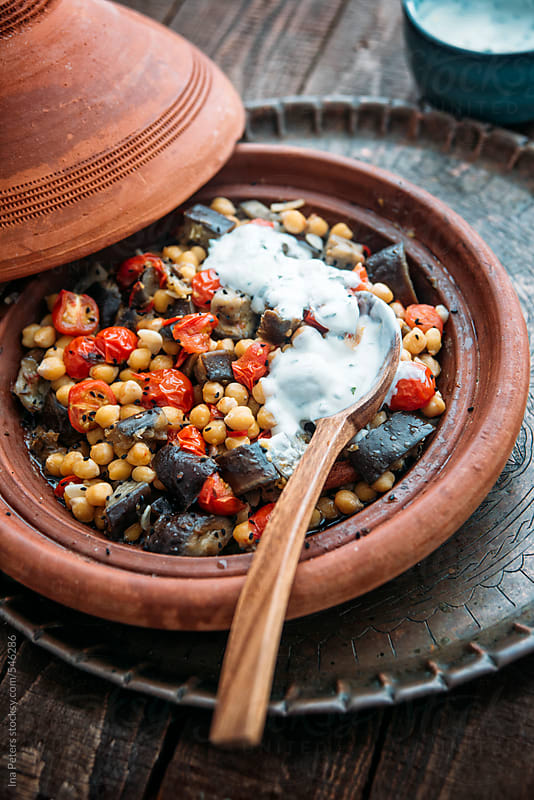 Food: Vegetarian Tagine with chickpeas, tomato and eggplant seved with lemon mint yogurt by Ina Peters for Stocksy United