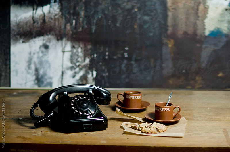 Old vintage black telephone with cup of coffee and tasty cookie by Marija Anicic for Stocksy United