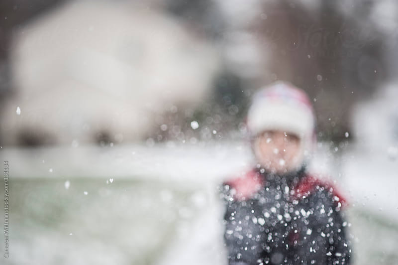 Boy throwing snow at camera blurred by Cameron Whitman for Stocksy United