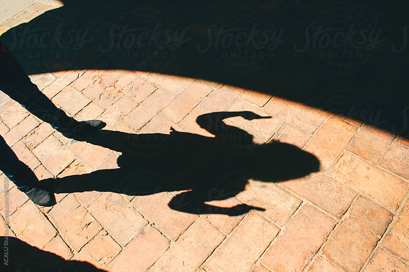 Shadow of a young woman with fingers raised by ACALU Studio for Stocksy United