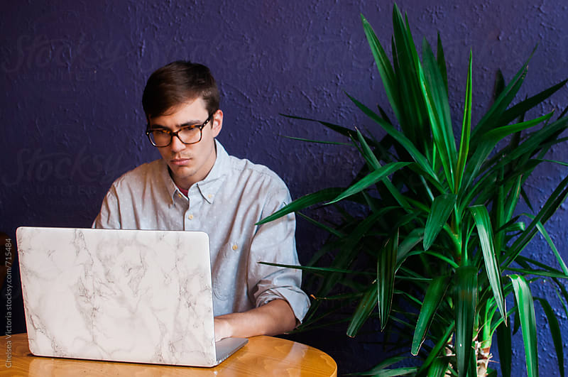 A young man sitting in a cafe using his laptop by Chelsea Victoria for Stocksy United