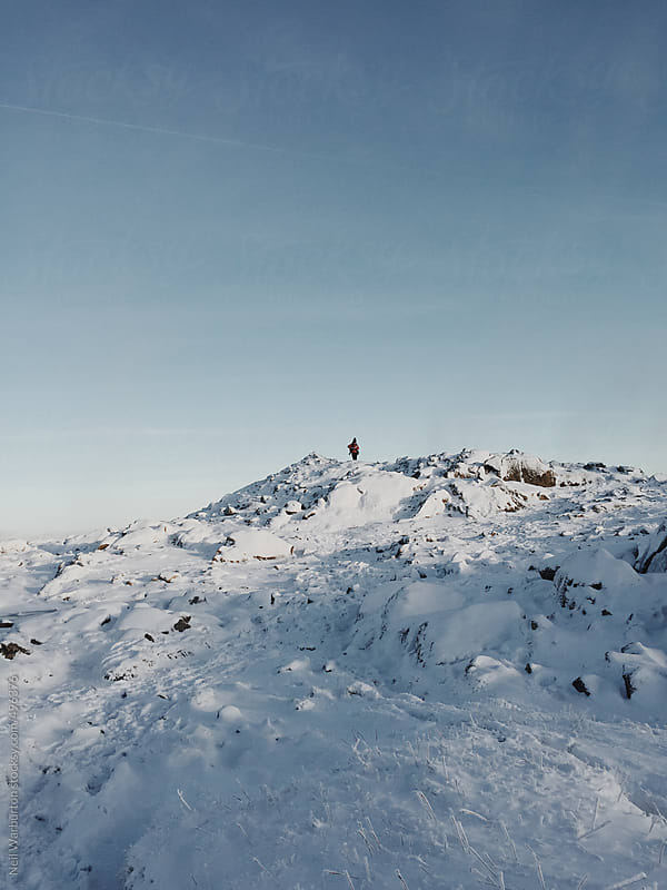 Hiker on mountain summit in winter by Neil Warburton for Stocksy United