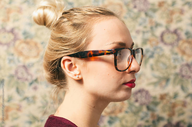 Side view of a blonde woman wearing glasses in front of a vintage wall. by BONNINSTUDIO for Stocksy United