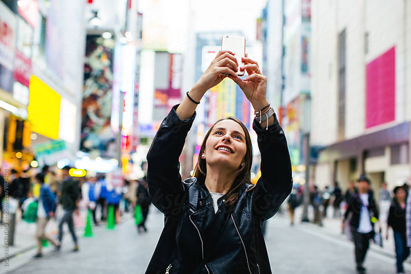 Portrait of a tourist taking a photo on the street. by BONNINSTUDIO for Stocksy United