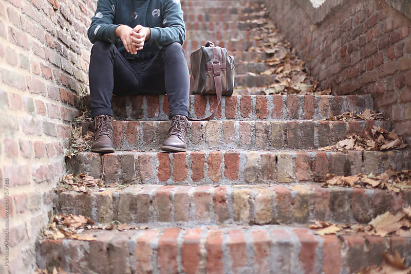 Cool guy sitting on stairs made of bricks by Painted Wood for Stocksy United