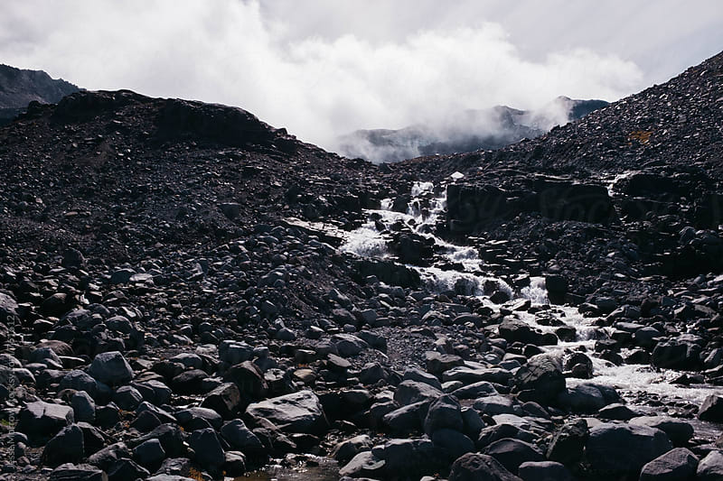 dark mountain rock with river and clouds rising above  by Jesse Morrow for Stocksy United