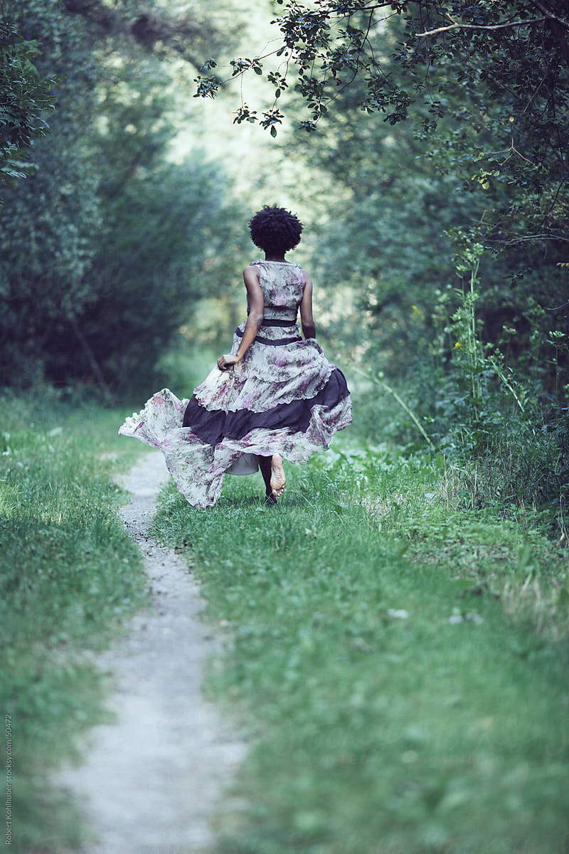 Black woman with dress running in forest by Robert Kohlhuber ...