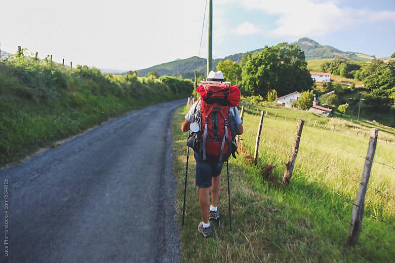 Hiker walking along the street, Way of St. James, Spain by Luca Pierro for Stocksy United