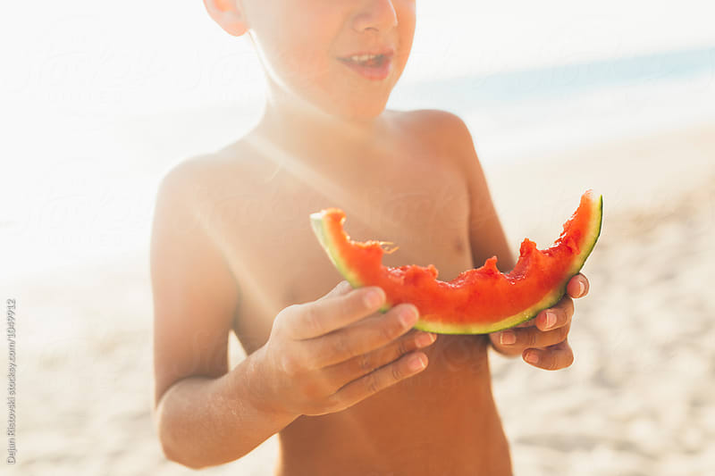 Boy eating a piece of watermelon at the beach. by Dejan Ristovski for Stocksy United