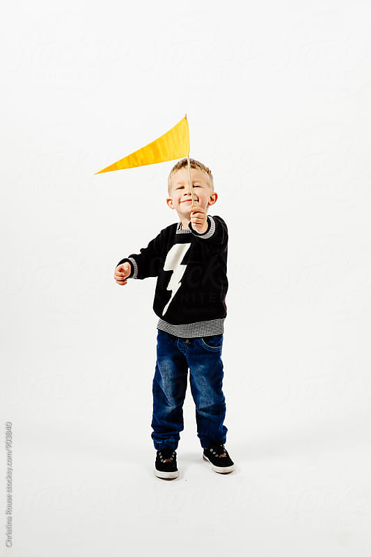 Boy holds up a fabric flag and smiles by Christina Rouse for Stocksy United