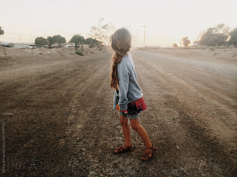 Young Girl Standing on Dirt Road at Sunset by Denise Bovee for Stocksy United