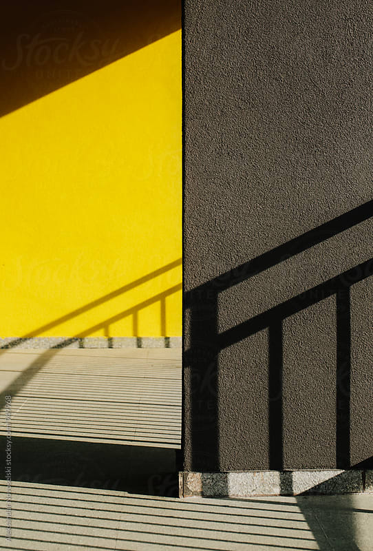 Harsh shadows of railing on yellow and black wall by Aleksandar Novoselski for Stocksy United