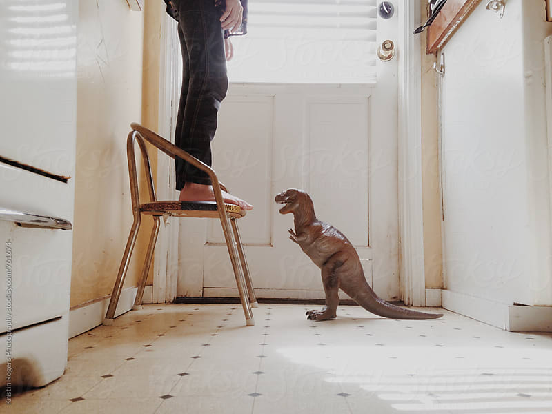 Child standing on chair with dinosaur  by Kristin Rogers Photography for Stocksy United