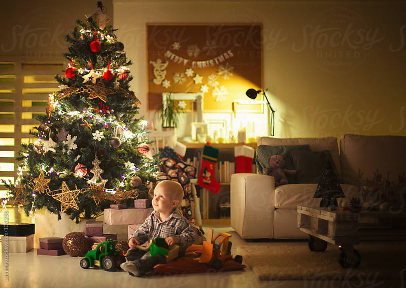 Cute Boy Playing by the Christmas Tree by Lumina for Stocksy United