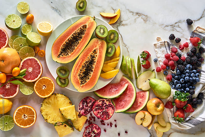 Various healthy fruits on marble table by Trent Lanz for Stocksy United