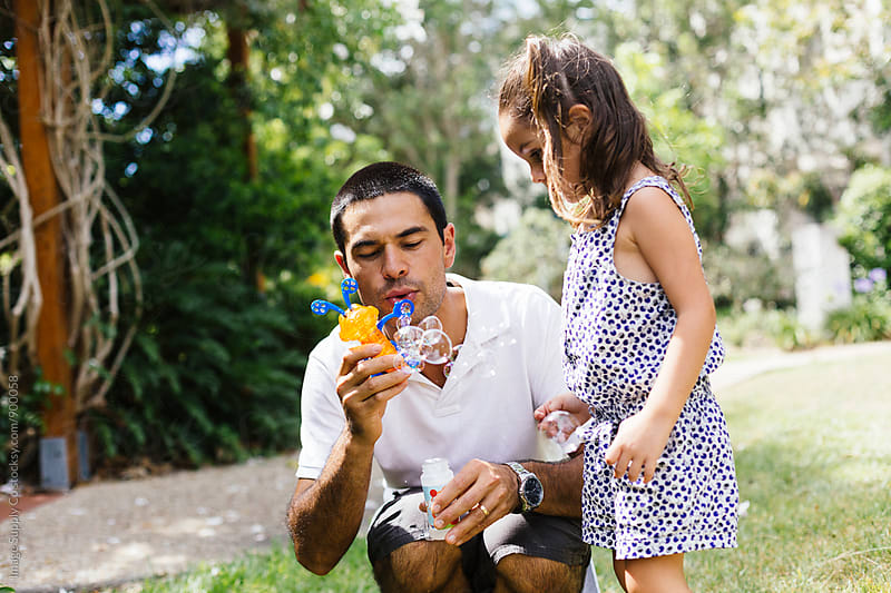Young father blows bubbles with his daughter in park. by Image Supply Co for Stocksy United