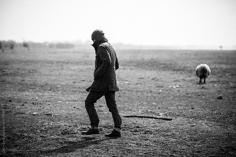 Man walking in dry field by Lior + Lone for Stocksy United