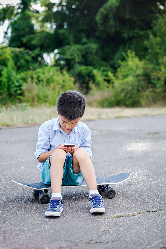 Asian kid sitting on his skateboard looking at a cellphone outdoor in a park by Suprijono Suharjoto for Stocksy United