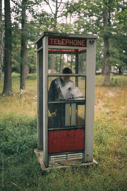 Phone Booth Smoke Man by Jake Elko for Stocksy United