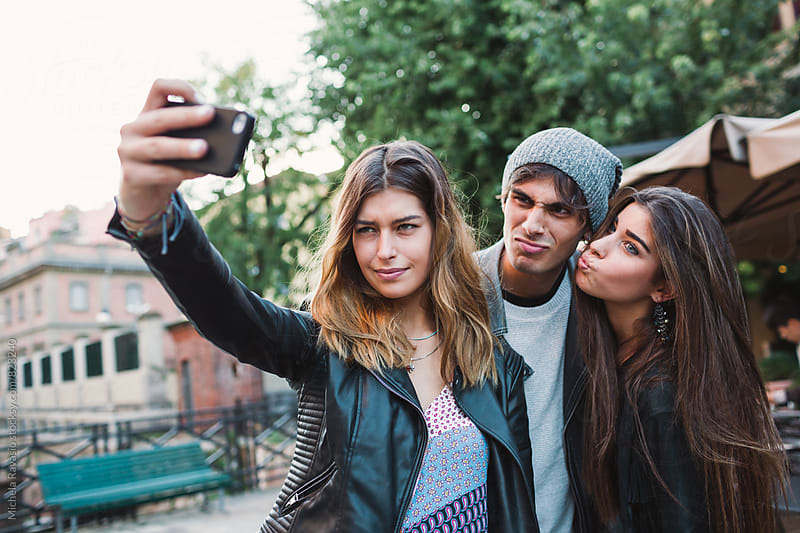 Friends taking funny selfie together by michela ravasio for Stocksy United