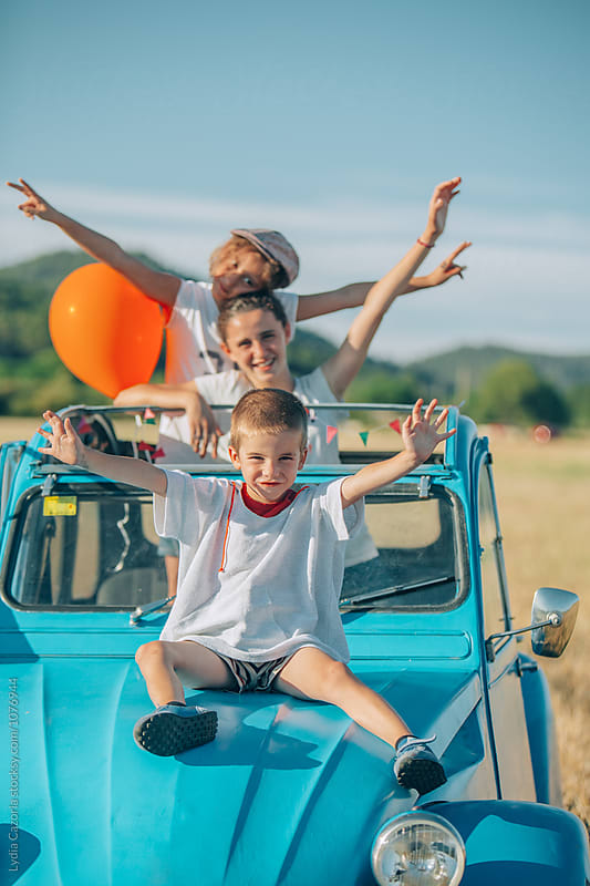 kids and teens uploaded on the vinatge car  in the countryside by Lydia Cazorla for Stocksy United