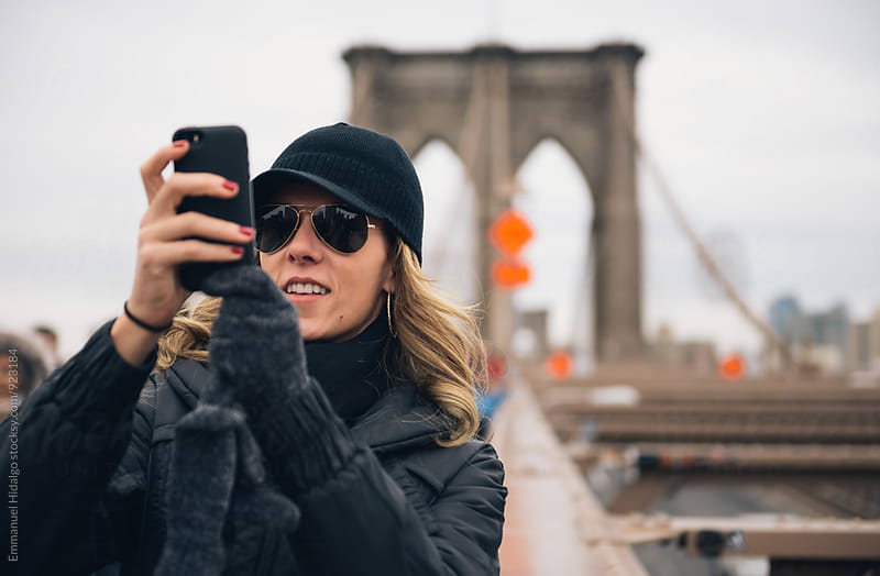 Woman taking a photo with her smart phone on the Brooklyn Bridge in New York by Emmanuel Hidalgo for Stocksy United