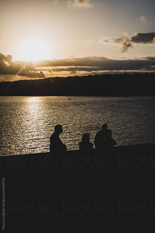 People looking at seascape at sunset by Mauro Grigollo for Stocksy United