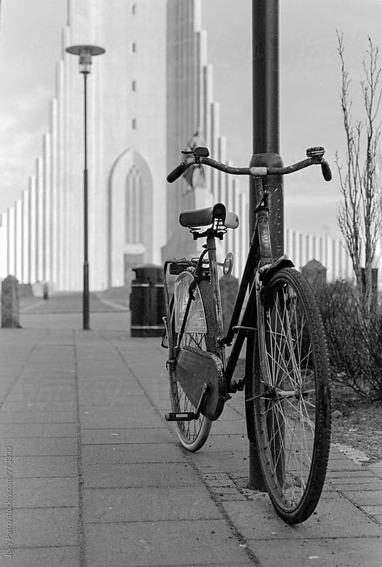 Rusted bicycle in front of Hallgrímskirkja Church, Iceland by Joey Pasco for Stocksy United