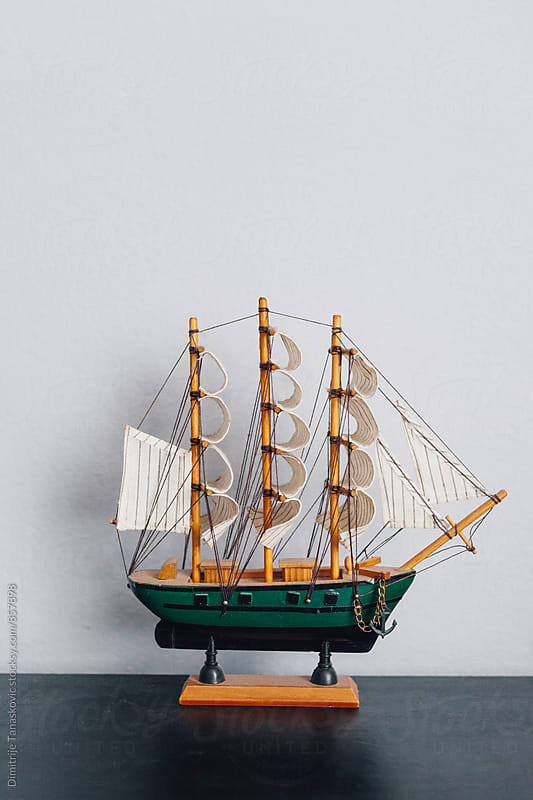 Small, wooden sailboat model on the table by Dimitrije Tanaskovic for Stocksy United