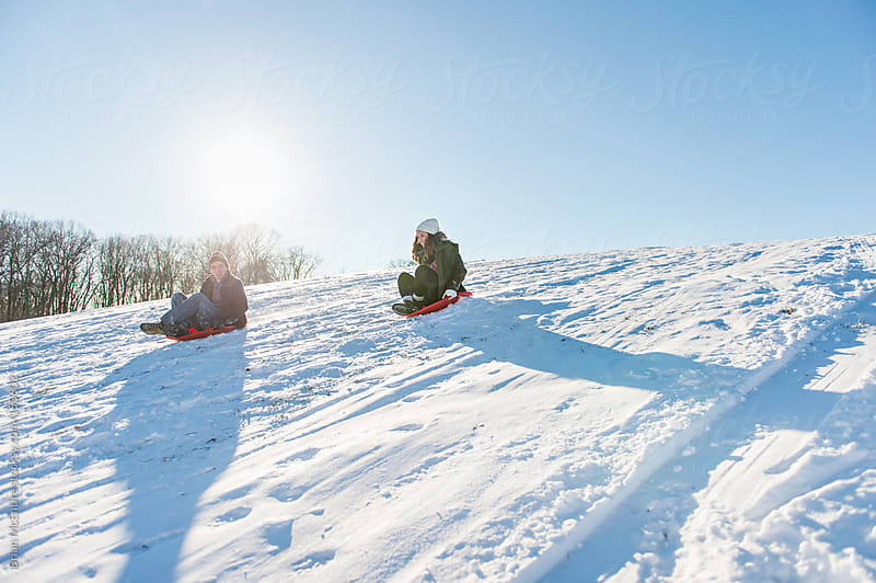 Late teen young adults race down a sledding hill on saucer sleds by Brian McEntire for Stocksy United