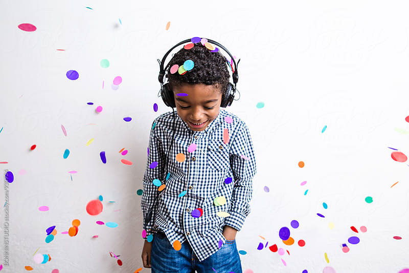 Little boy listening music whilst confetti falls from above. by BONNINSTUDIO for Stocksy United