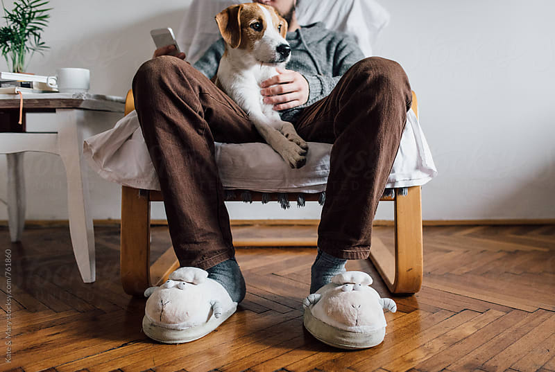 Man sitting and holding a dog by Katarina Simovic for Stocksy United