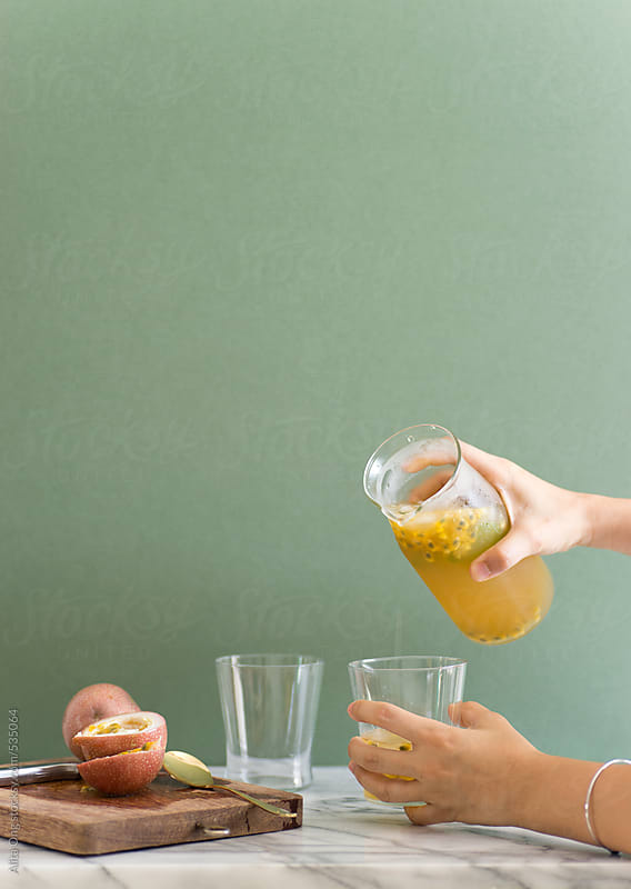 Hands pouring passion fruit juice by Alita Ong for Stocksy United