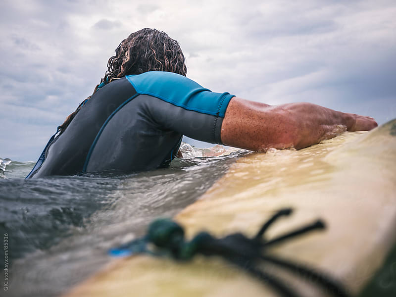 Surfer holding the board in the ocean by GIC for Stocksy United