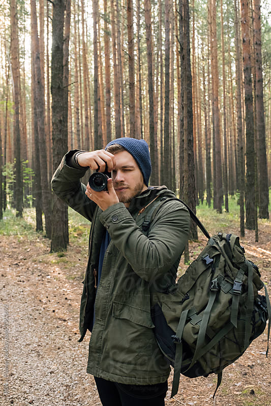 Portrait of cameraman with backpack photographing in forest by Danil Nevsky for Stocksy United