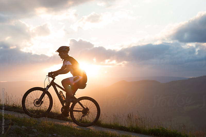 Man riding a bike uphill against sunset sky by RG&B Images for Stocksy United
