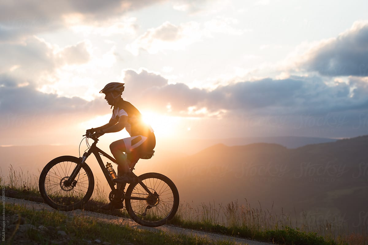 man riding a bike uphill against sunset sky stocksy united