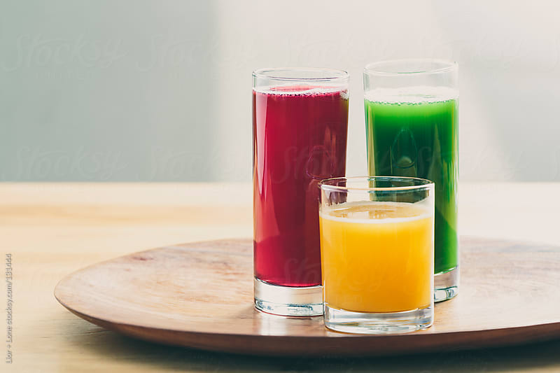 Three colorful juices on a wooden tray by Lior + Lone for Stocksy United