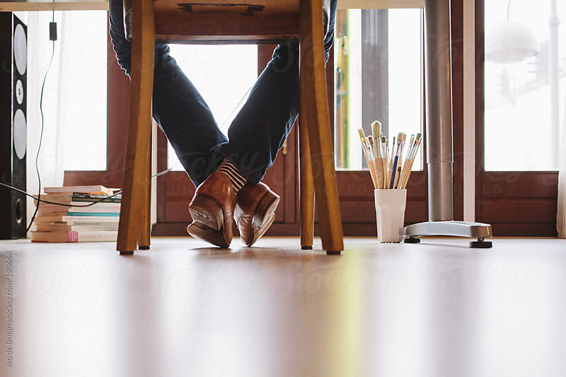 Legs of someone sitting behind his desk at home by Ivo de Bruijn for Stocksy United