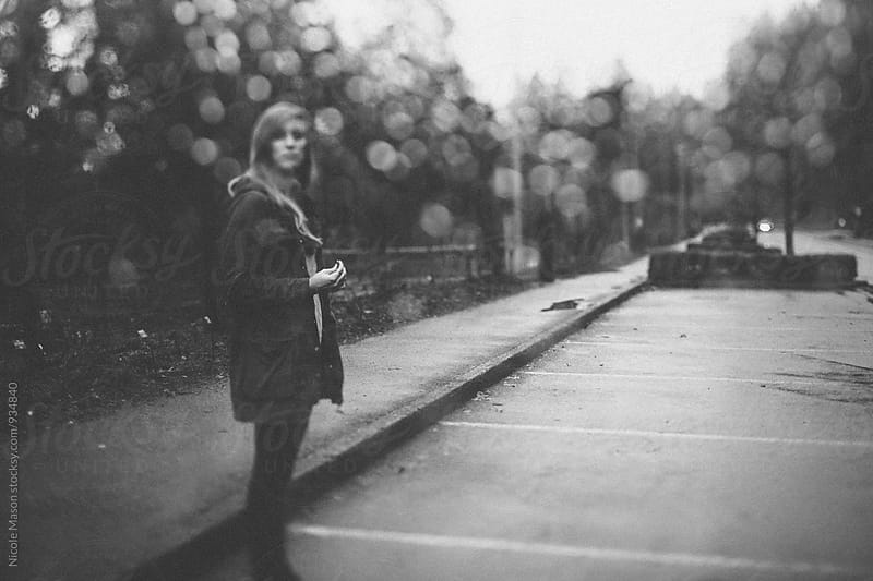 woman standing in parking lot on rainy day by Nicole Mason for Stocksy United