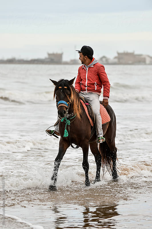 Horse Riding on the beach in winter by Bisual Studio for Stocksy United