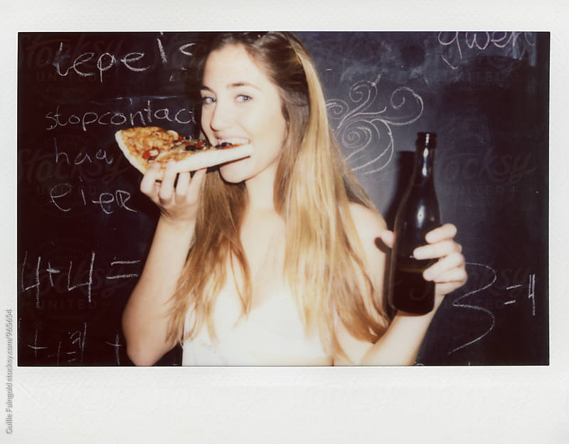 Portrait of young girl looking at camera while biting pizza by Guille Faingold for Stocksy United